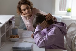 Loving mother supporting tired teenage daughter study together at home. Worried young parent mom helping comforting sad teen encouraging school girl having difficulty with education learning at home.
