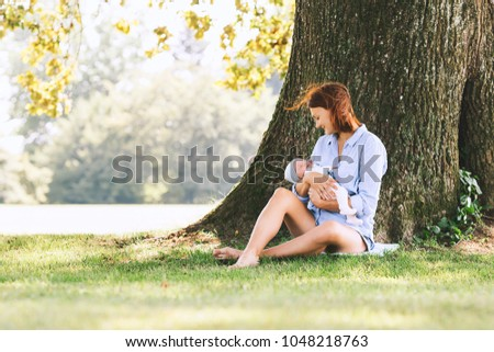Loving mother with her newborn baby on her arms. Beautiful mom with a cute sleeping new born child on nature outdoors. Baby's first week of life. Happy maternity and harmonious family.