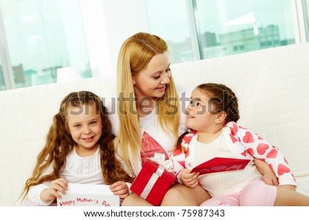Loving mother with her two pretty daughters interacting at home