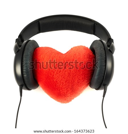 Loving music concept as a headphones put on a plush red heart composition, isolated over white background