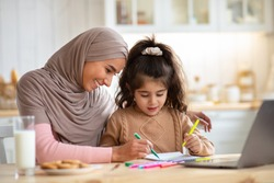 Loving Muslim Mom In Hijab Drawing With Her Little Preschooler Daughter In Kitchen, Happy Islamic Family Sitting At Table And Using Colorful Pencils, Having Fun Together At Home, Free Space