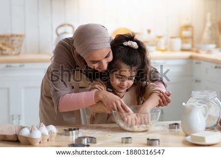 Loving Muslim Mom Teaching Daughter How To Knead Dough, Having Fun Together In Kitchen At Home, Woman In Hijab Helping To Her Little Child, Islamic Family Enjoying Making Homemade Pastry, Free Space