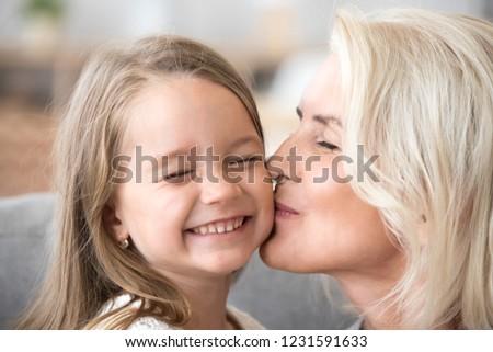 Loving old aged grandmother kissing cute preschool granddaughter on cheek, smiling grandchild girl enjoying care of happy senior mature grandma, two generations granny and kid warm relations