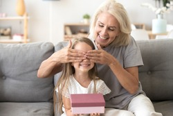 Loving old grandmother making present to little happy kid girl holding gift box, middle-aged granny closing eyes of cute smiling grandchild excited with birthday surprise from grandma sitting on sofa