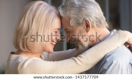 Loving old senior family couple bonding embracing touching foreheads, romantic middle aged mature man and woman hugging getting closer enjoying moment of affection cuddling, close up side view