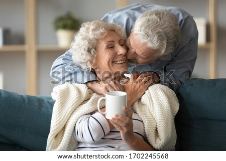 Loving older husband kissing smiling wife on cheek, covering warm plaid, expressing love and care, aged senior couple enjoying tender moment, mature woman holding cup of tea coffee, relaxing on sofa