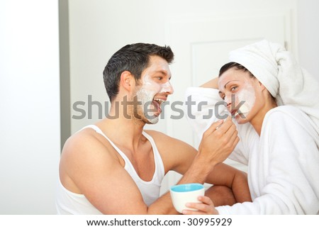 Loving pair couple making cosmetics at home. girlfriend applies beauty mask to husband in living room