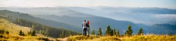 Loving pair standing on a hill, enjoying beautiful mountain landscape with morning haze over the mountains and forests. Man embracing woman, she is covered with a plaid. Back view. Panorama