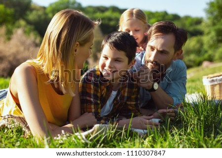 Loving parents. Alert bearded daddy smiling and lying on the cover with his family #1110307847