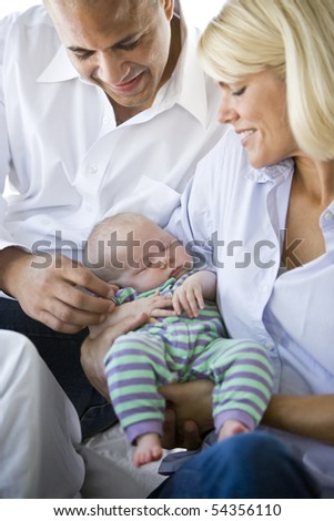 Loving parents holding 3 month old baby sound asleep in arms