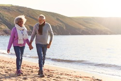 Loving Retired Couple Holding Hands As They Walk Along Shoreline On Winter Beach Vacation