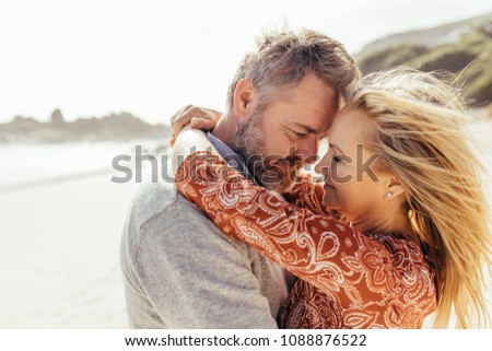 Loving senior couple embracing each other on the beach. Mature man and woman hugging outdoors.