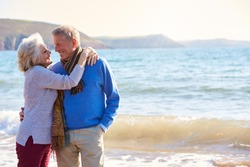 Loving Senior Couple Hugging As They Walk Along Shoreline Of Beach By Waves