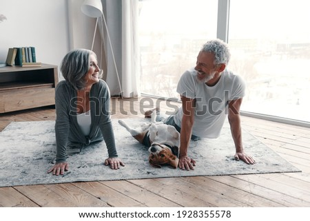 Loving senior couple in sports clothing doing yoga and smiling while spending time at home with their dog Сток-фото ©