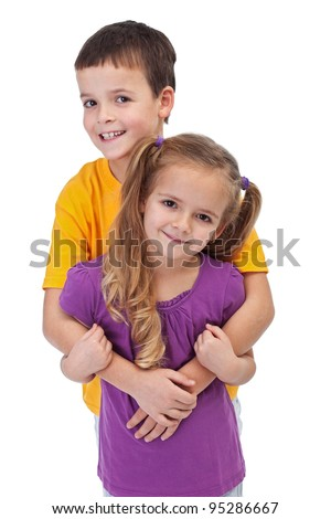 Loving siblings - little boy hugging his smaller sister, isolated