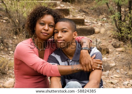 Loving single-mother hugging her handsome teenage son