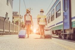 Loving tourists holding suitcases at the train station. Two young person are ready to get on the train and begin their journey