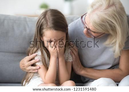 Loving understanding old grandma embracing little crying girl comforting upset granddaughter, senior caring grandmother hugging child consoling kid in tears, grannys empathy support for grandchild