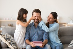 Loving wife and kid daughter making surprise to smiling dad receiving gift on fathers day, family closing eyes of excited daddy preparing present congratulating celebrating happy birthday at home