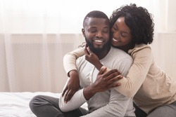 Loving wife cuddling husband from the back while sitting on bed together, enjoying weekend. Copy space