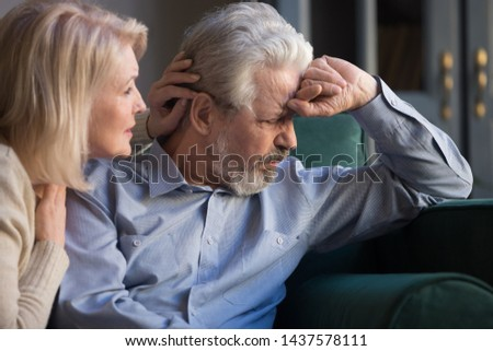 Loving worried middle aged wife supporting comforting apologizing sad senior elder husband helping with problem asking for forgiveness sit on sofa, old retired couple apology compassion support