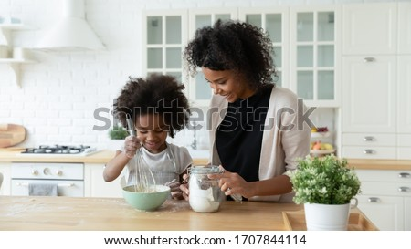 Loving young African American mother teach small biracial daughter bake in kitchen, happy caring ethnic mom and little girl child preparing pancakes or biscuits, make breakfast at home together ストックフォト ©