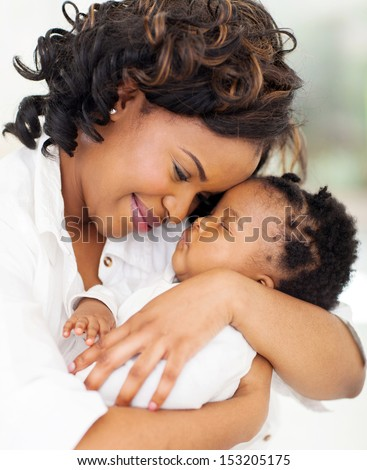 loving young african mother holding her asleep baby