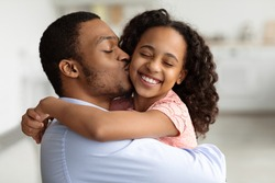 Loving young black dad kissing and hugging his beautiful little daughter, closeup portrait. Happy little girl and her handsome father having fun together at home. Fatherhood, parenthood concept