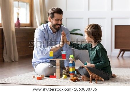 Loving young Caucasian dad sit on floor play with small son give high five celebrate success. Happy caring father engaged in activity game build with blocks bricks with little boy child together. Stock photo ©