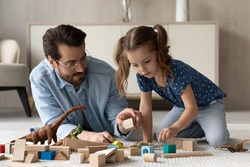 Loving young Caucasian father lying on floor in living room playing with small daughter. Caring dad relax on family weekend with little girl child engaged in playful activity with blocks and bricks.
