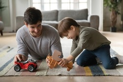 Loving young Caucasian father lying on warm floor play toys cars with excited little preschooler son, happy dad have fun relax involved in game activity with automobiles planes with small boy child