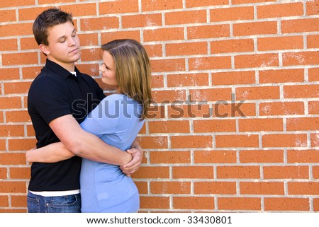Loving young couple against a brick wall