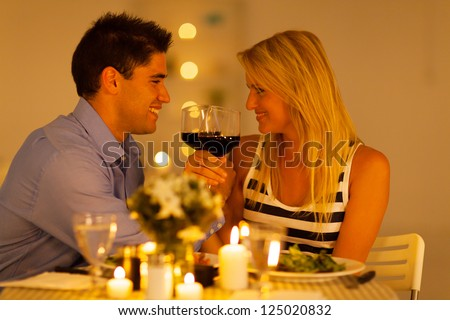 loving young couple enjoying a glass of wine in restaurant