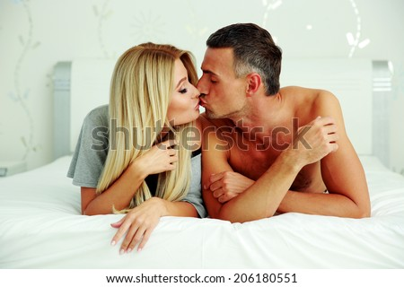 Loving young couple lying on the bed and kissing  #206180551