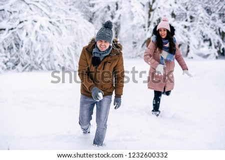 Loving young couple playing with snowballs in a winter park. Family love and care concept.