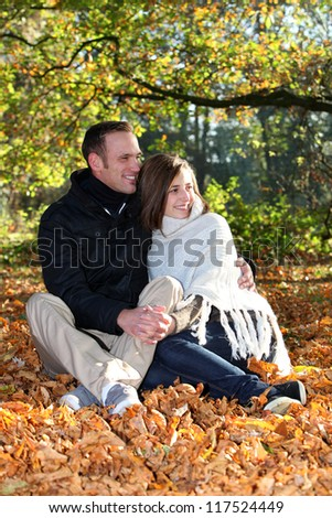 Loving young couple sitting in a close embrace sharing an intimate moment together as they enjoy the solitude of an autumn forestr