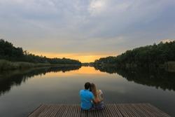 Loving young couple sitting near a lake