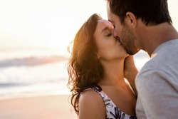 Loving young couple standing in each other's arms and kissing on a sandy beach at dusk