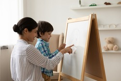 Loving young Indian mom and little ethnic son draw paint together on flip chart at home. Happy mixed race mother play learn study with small biracial boy child on whiteboard. Funny education concept.