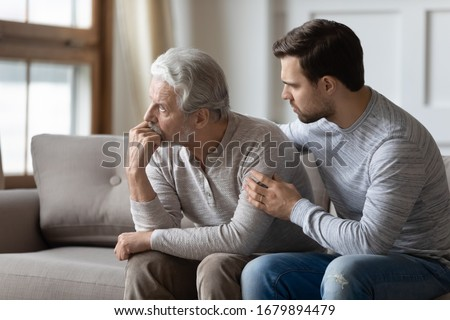 Loving young man embrace comfort upset elderly gray-haired dad suffering from depression or problems, caring adult grown-up son hug caress support mature father feeling lonely distressed at home Сток-фото ©