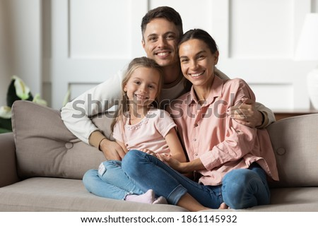Photo of  Loving young man hug his beloved wife and little daughter sit on couch in living room, happy people smiling looking at camera posing for photo picture. Exemplary family portrait, love and bond concept