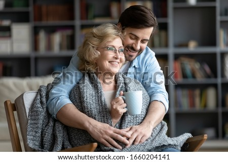 Loving young man take care of happy middle-aged mother sit in chair drinking tea enjoying family weekend in living room, thankful grown-up adult son hug show gratitude and affection to mature mom