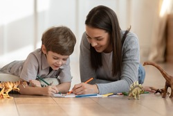 Loving young mom or nanny lying on warm floor drawing in album with little boy child, smiling mother have fun play paint on paper with small son on home family weekend, children creativity concept