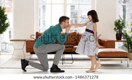 Loving young single dad standing on knee kissing hand of adorable cute little daughter thanking for dance, happy father playing with small kid girl princess having fun pretend ball at home together #1486371278