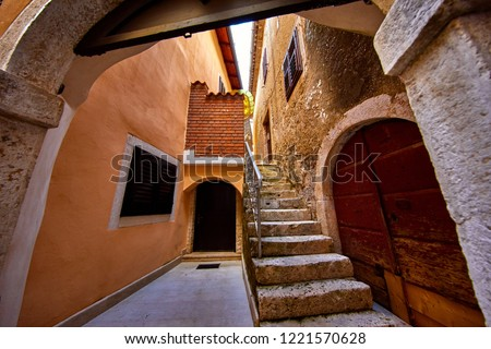 Lovran, Istria, Croatia. Vintage medieval buildings and houses at narrow lanes of old town. Stone stairs, wooden doors and windows. Decorative arch between brick walls.