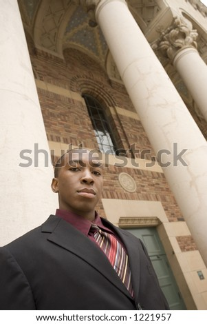 Low angel view of a business man in front of pillars