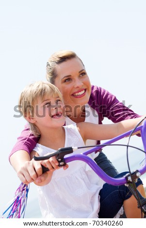 low angel view of happy mother teaching little girl how to ride a bicycle