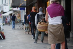 Low angle and selected focus, European people queue and wait for shopping on sidewalk outside supermarket during quarantine for COVID-19 virus in Düsseldorf, Germany.