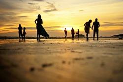 Low angle and selective focus shot of silhouettes of beach goers enjoying the sunset at Tanjung Aru beach, Kota Kinabalu, Sabah.