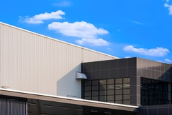 Low angle and side view of brown office on white corrugated metal industrial building against white clouds in blue sky background